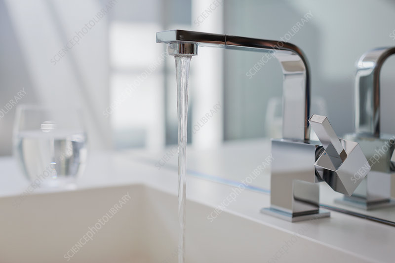 Water falling from modern bathroom faucet