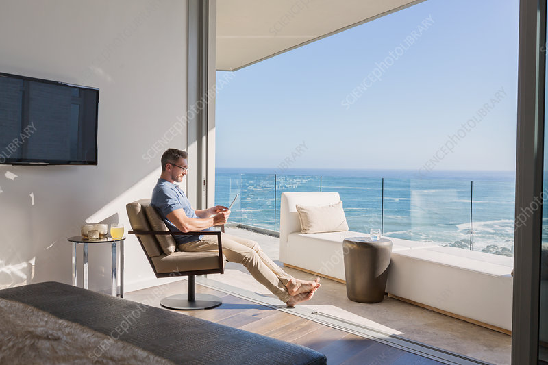 Man using digital tablet overlooking ocean view