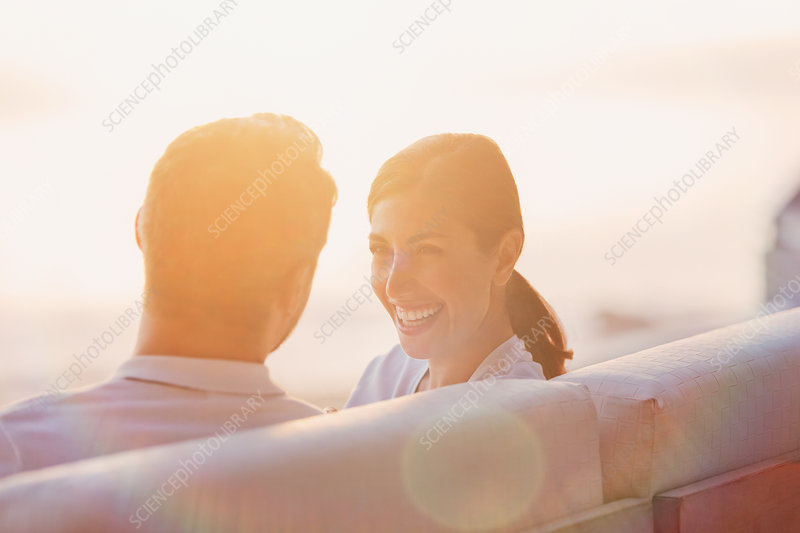 Smiling couple talking on sunset balcony