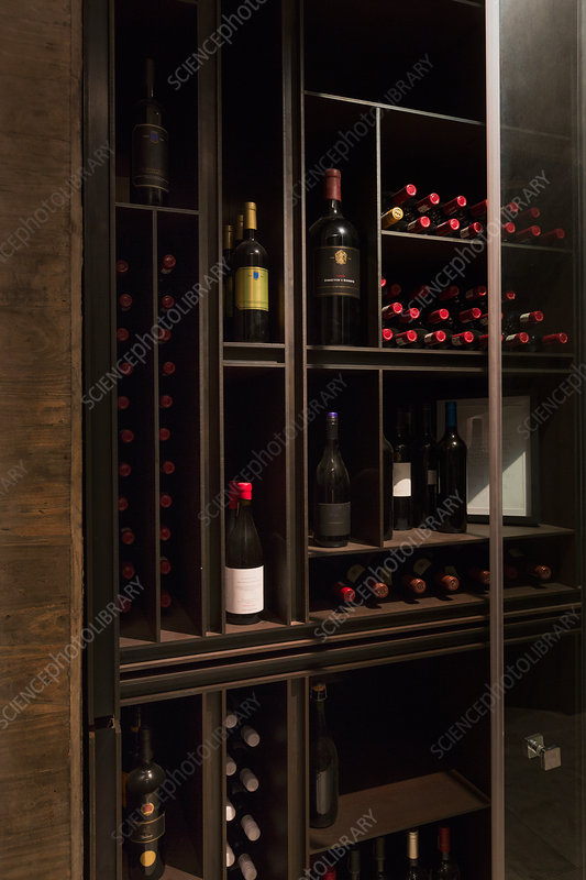 Wine bottles organized on wooden shelves