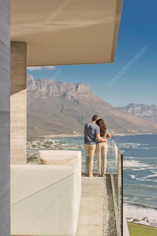 Couple looking at sunny ocean and mountain view