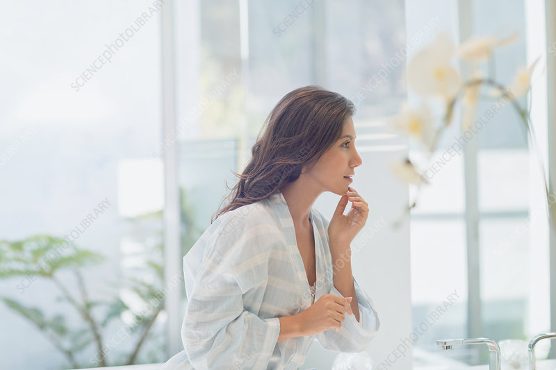 Brunette woman touching chin at bathroom mirror