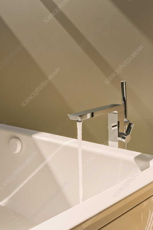 Water falling from modern bathtub faucet
