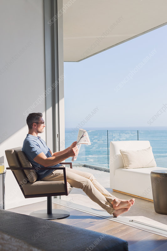 Man relaxing reading newspaper