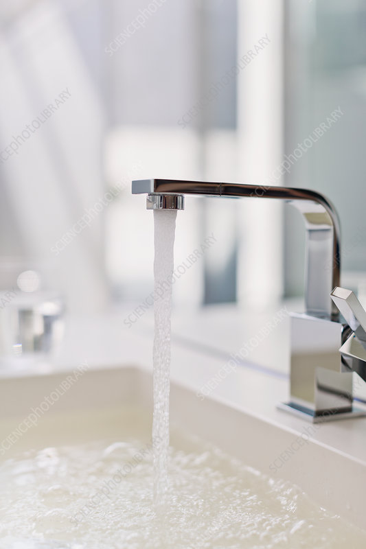 Water from modern faucet filling bathroom sink