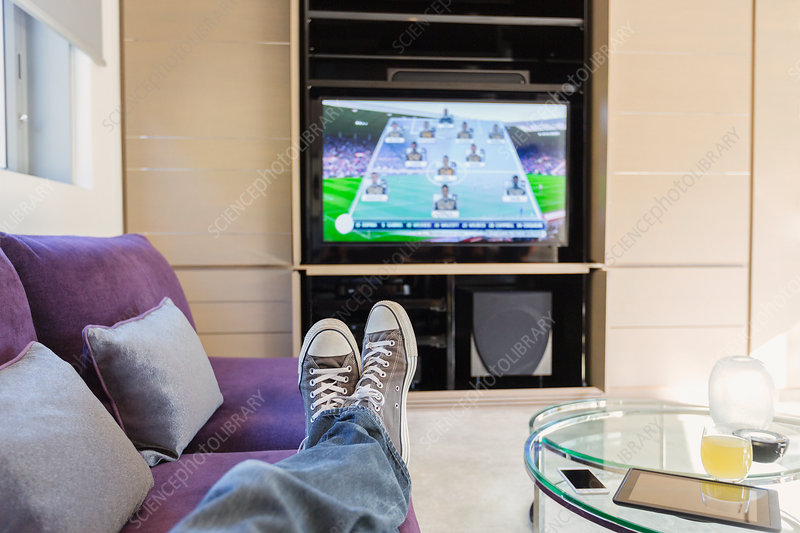 Man with feet up watching TV