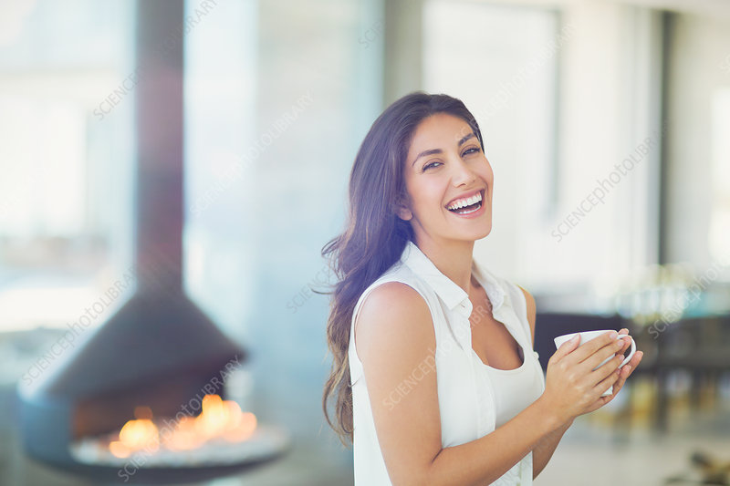 Woman drinking coffee near fireplace