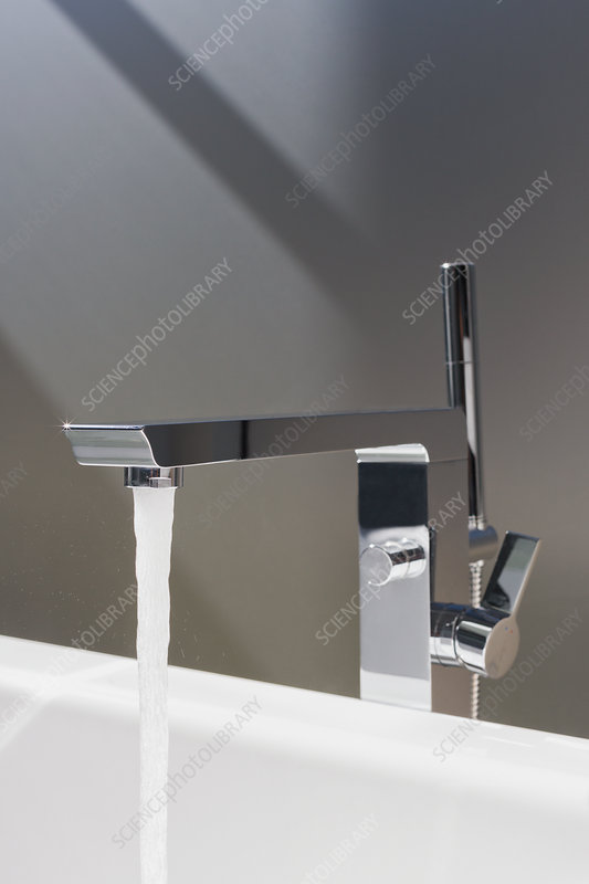 Close up water falling from modern bathroom faucet