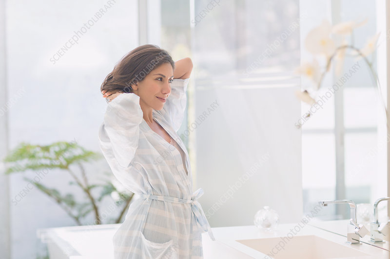 Brunette woman stretching at bathroom mirror