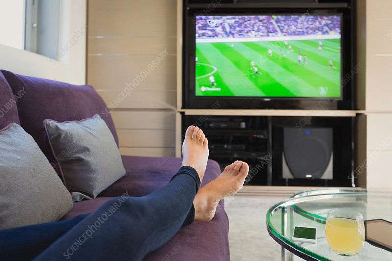 Woman with bare feet up watching TV