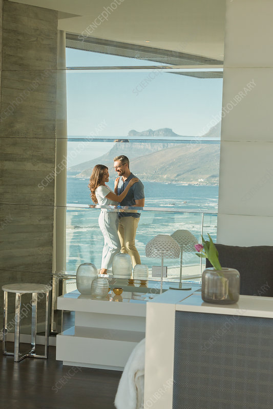 Reflection of couple hugging on luxury balcony