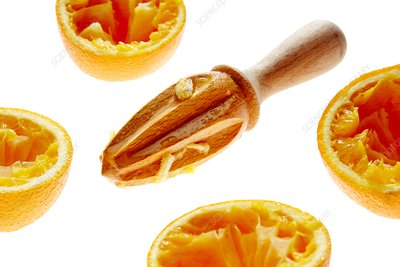 Orange halves and wooden juicer