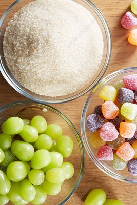 Bowls with sweets, grapes and sugar
