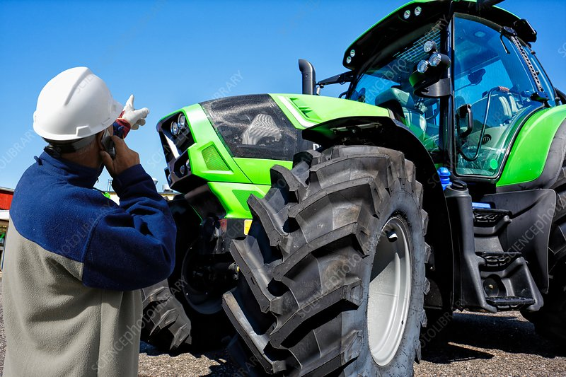 Mechanic on the phone pointing at tractor