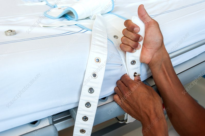 Nurse fastening medical restraint to hospital bed