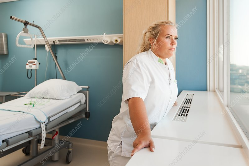 Female nurse looking out of window