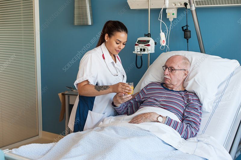 Female nurse giving male patient fruit juice