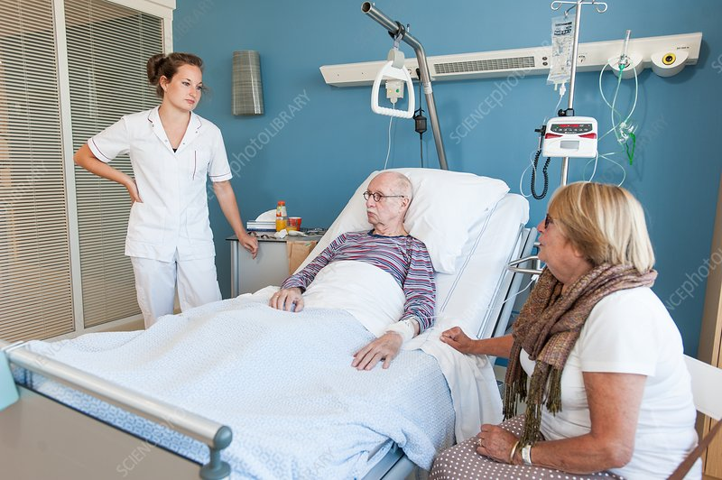 Female visitor and nurse talking to senior man