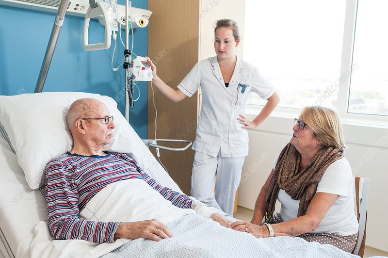 Woman visiting senior man , nurse listening