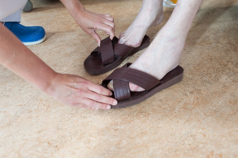 Nurse helping male patient to put sandals on