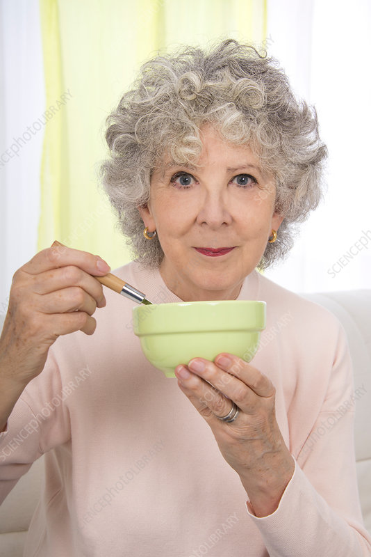 Woman eating from a bowl with a spoon