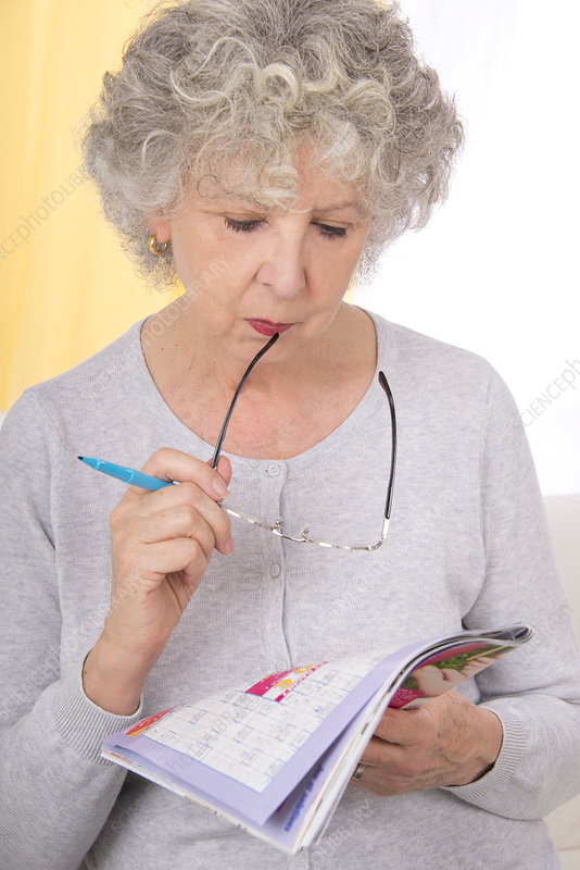 Woman reading magazine holding glasses