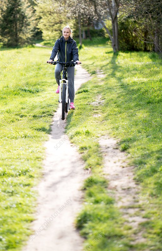 Woman riding bicycle on dirt track