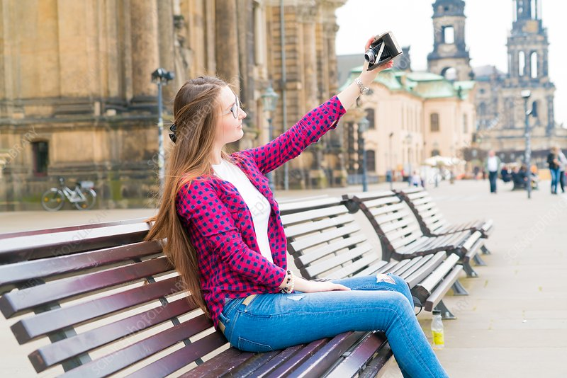 Young woman taking photo of herself with camera