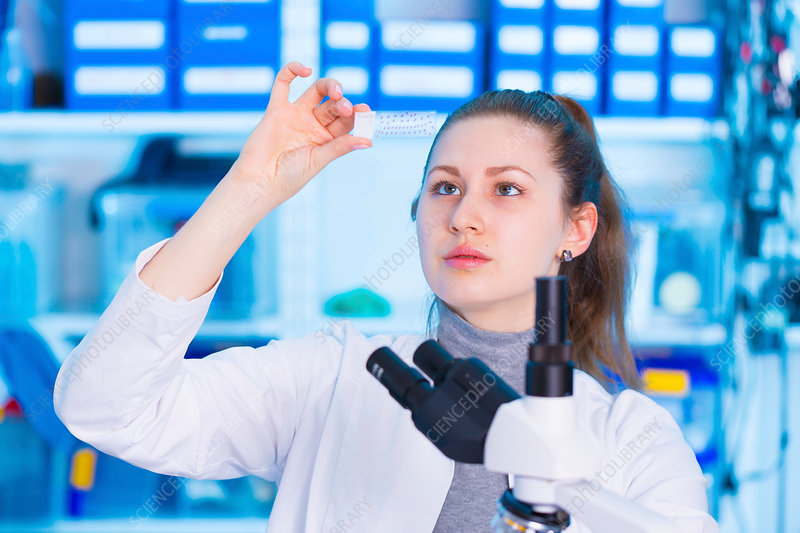 Woman looking at microscope slide