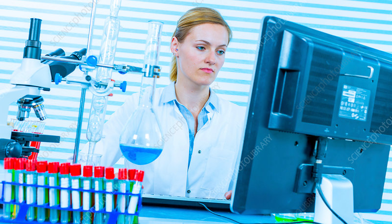 Woman using computer in chemical laboratory