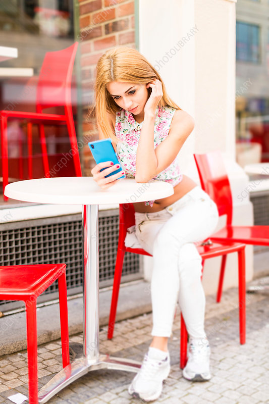 Young woman using smartphone in outdoor cafe