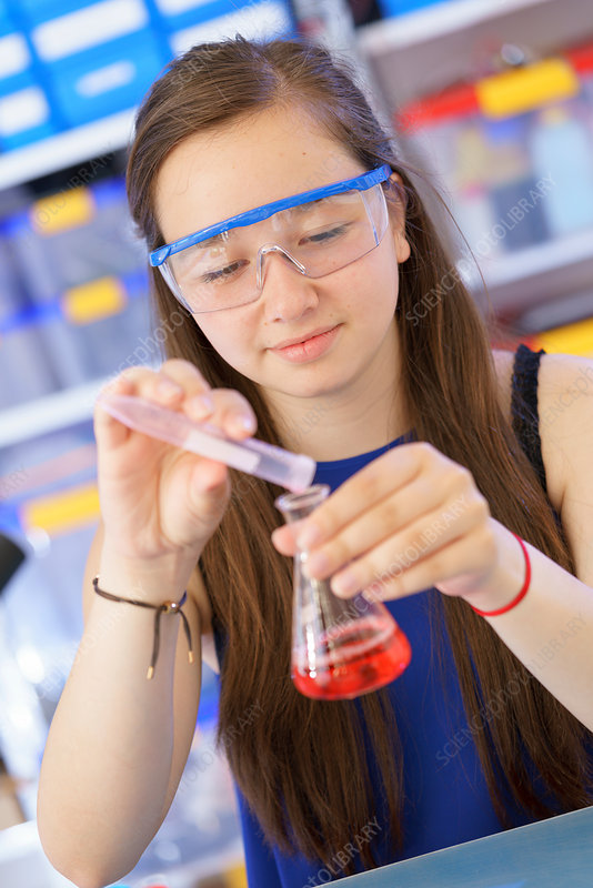 Girl pouring liquid into chemical flask