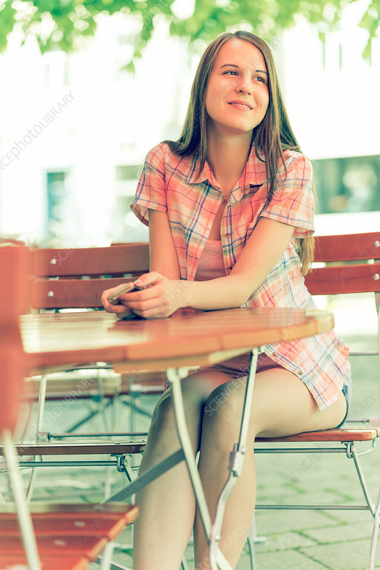 Young woman sitting on chair at pavement cafe