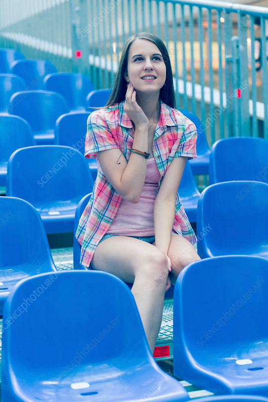 Young woman sitting on blue plastic seat