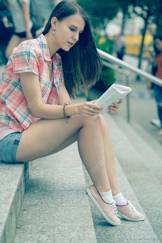 Young woman sitting on steps reading notes