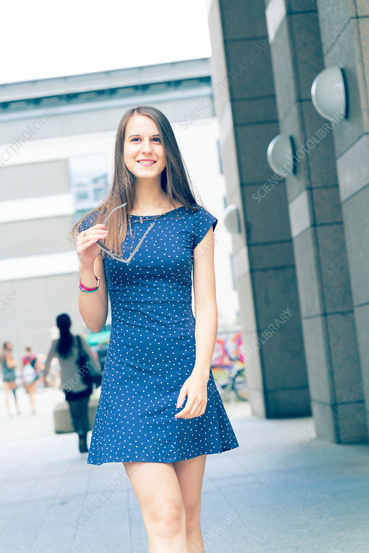 Young woman in short blue dress by buildings