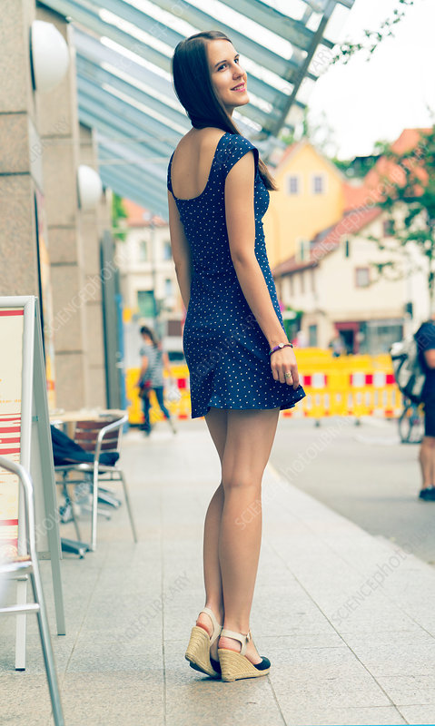 Young woman in short blue dress on pavement
