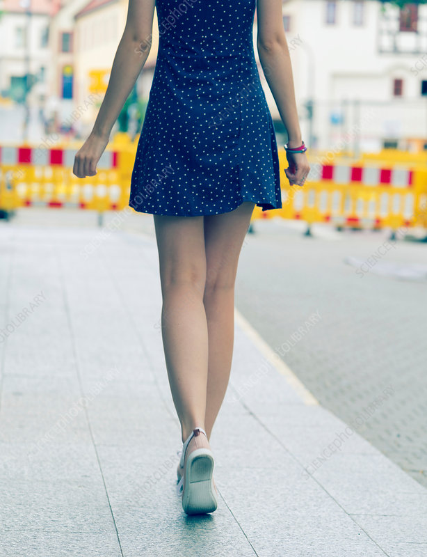 Young woman in short dress walking on pavement