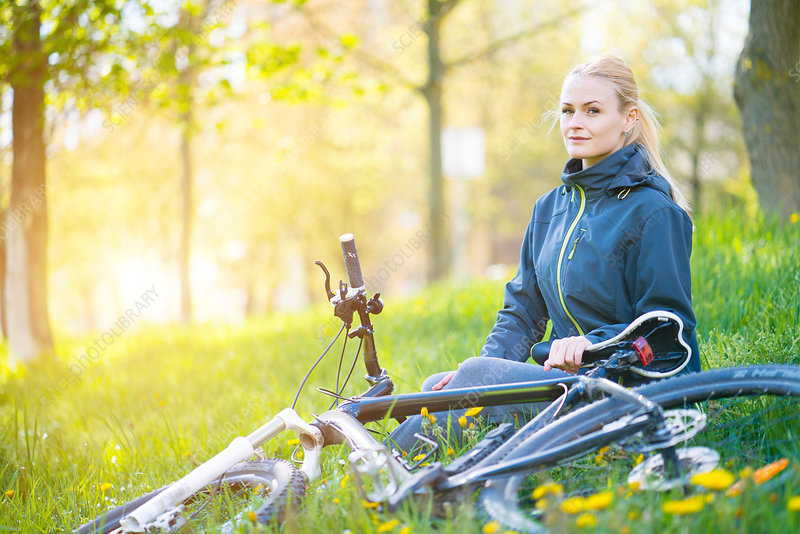 Woman sitting in woods with bicycle