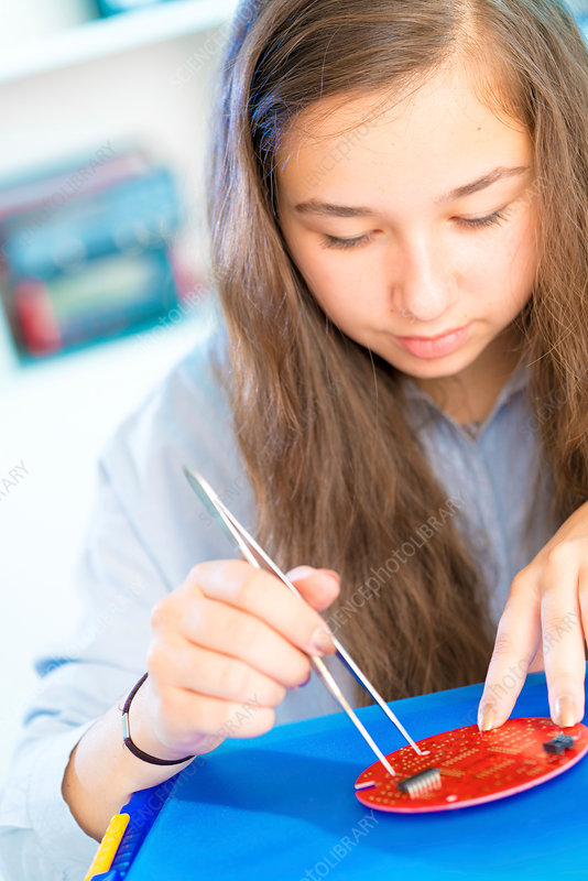 Girl using tweezers with circuit board