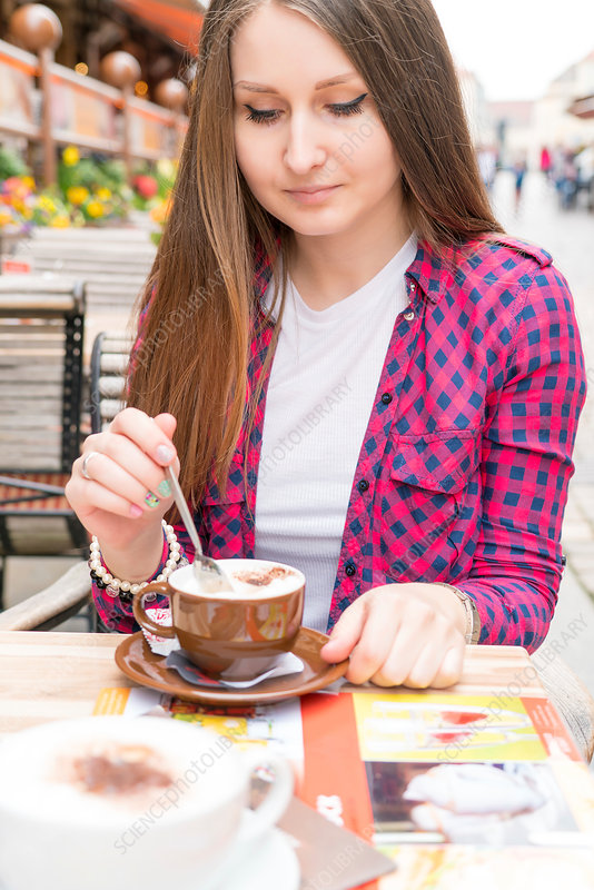 Young woman with hot drink at outdoor cafe