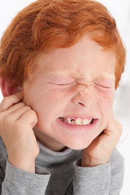 Boy putting fingers in ears with eyes closed