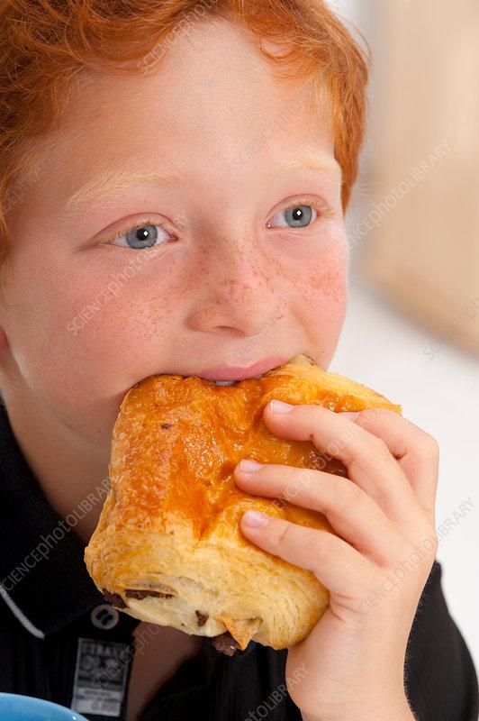Boy eating pain au chocolate