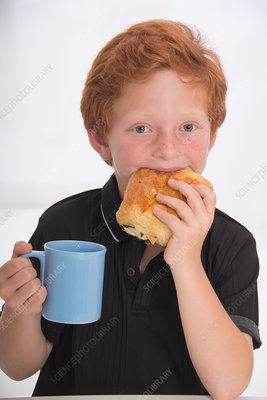 Boy eating food and holding mug