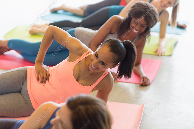Smiling women doing side planks in exercise class