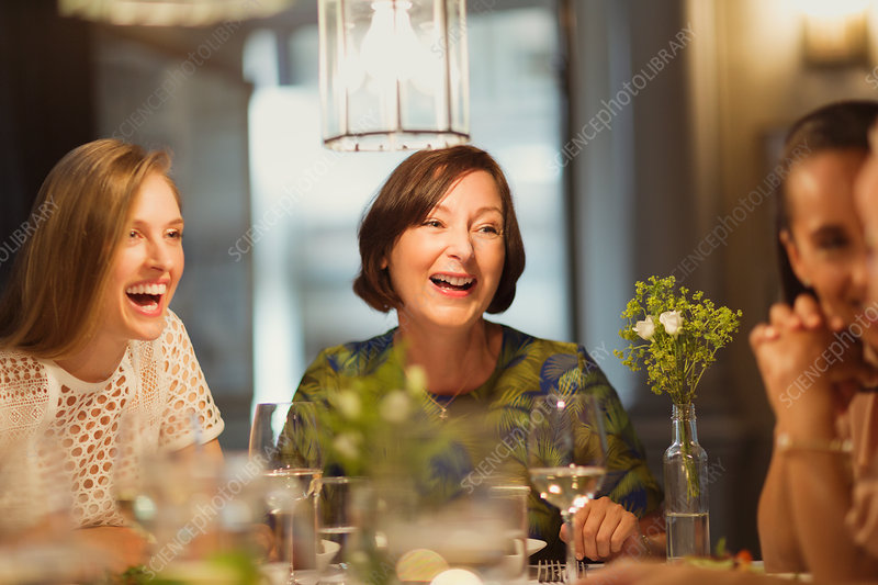 Laughing women friends dining and talking