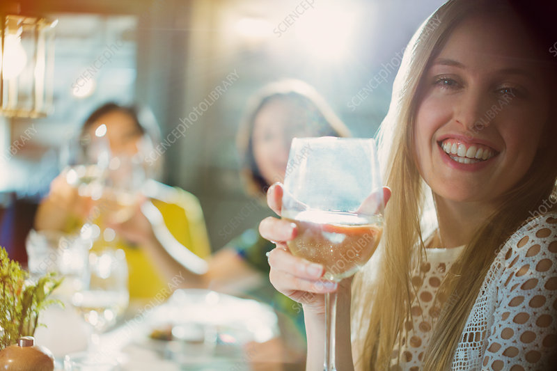 Portrait smiling woman drinking white wine dining