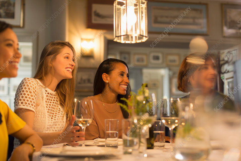 Smiling women friends dining and drinking wine