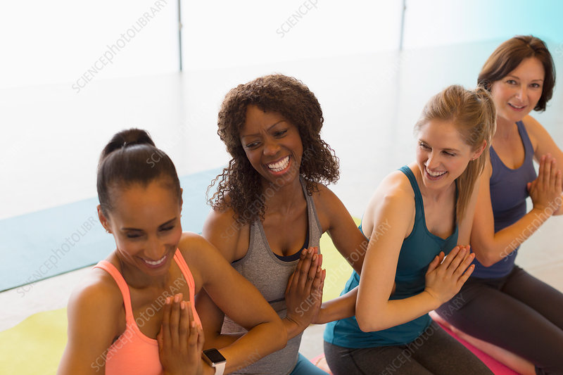 Smiling women practicing yoga with hands