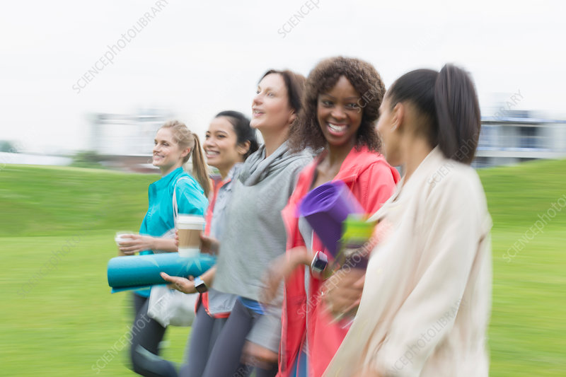Smiling friends walking with yoga mats and coffee